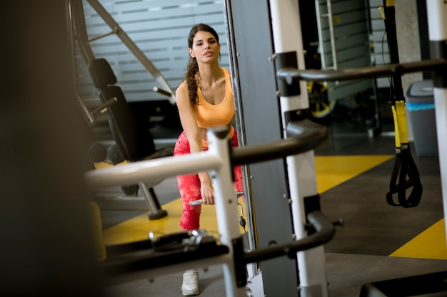Woman using straight bar cable to pull up weights to exercise biceps in the gym Premium Photo