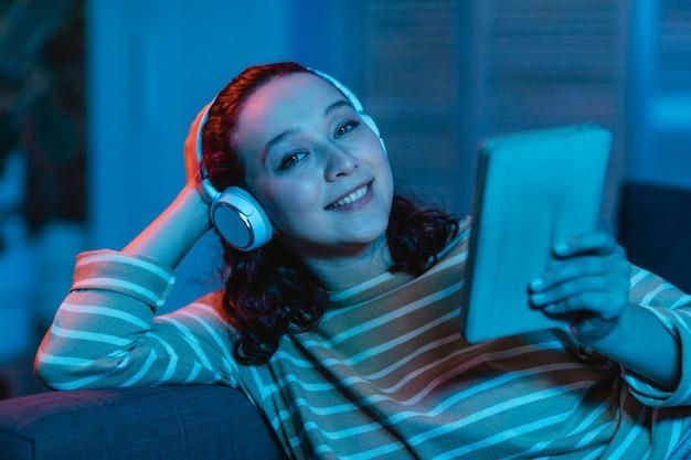 여자 집에서 태블릿 및 헤드폰을 사용하여 소파에 무료 사진