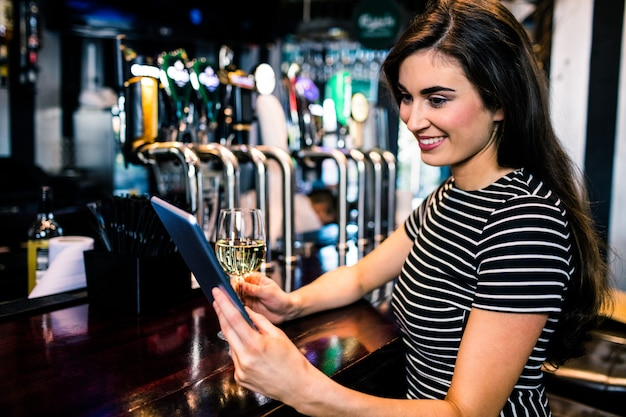 Woman using tablet and having a glass of wine in a bar Premium Photo