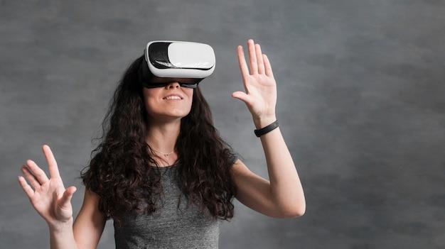 Woman using virtual reality headset front view Free Photo