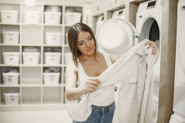 Woman using washing machine doing the laundry. young woman ready to wash clothes. interior, washing process concept Free Photo
