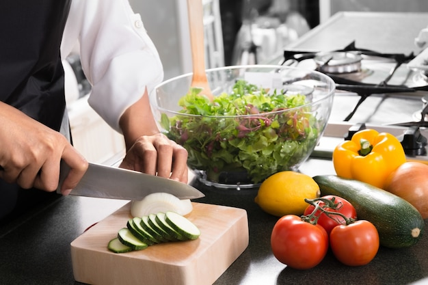 Woman vegan cooking healthy food and preparing salad for dinner in a kitchen Premium Photo