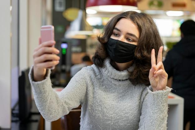 Videochiamata della donna mentre indossa la mascherina medica Foto Gratuite