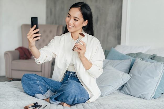 メイクブラシについてビデオブログをしている女性 無料写真