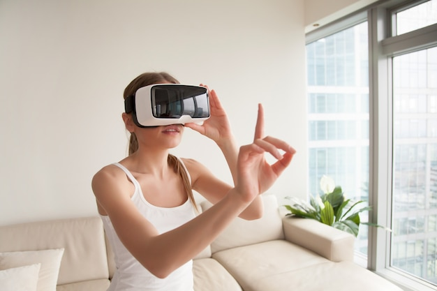 Woman in vr headset touching virtual objects Free Photo