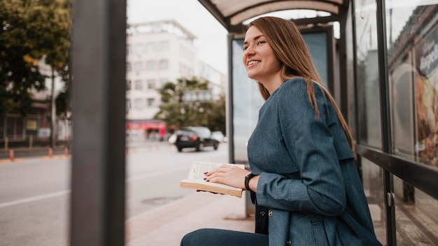 Woman waiting for the bus and holding a book Free Photo