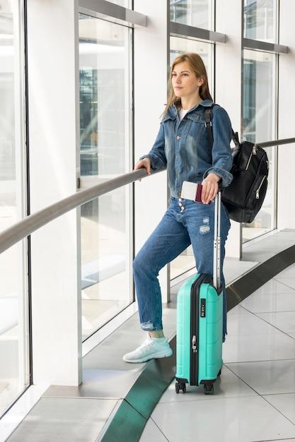 Женщина ждет своего рейса с чемоданом Бесплатные Фотографии