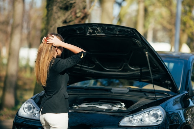 A woman waits for assistance near her car broken down on the road side. Free Photo