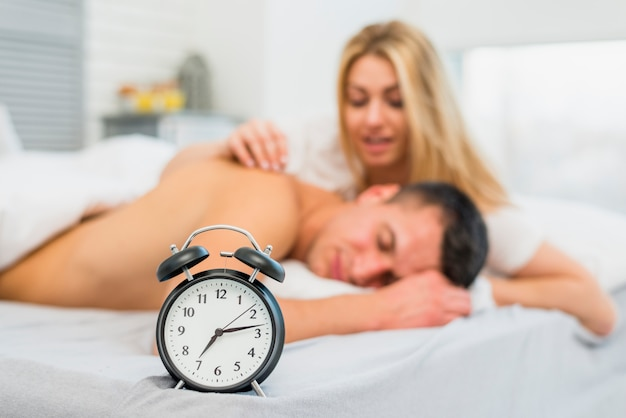 Woman waking up man near snooze in bed Free Photo