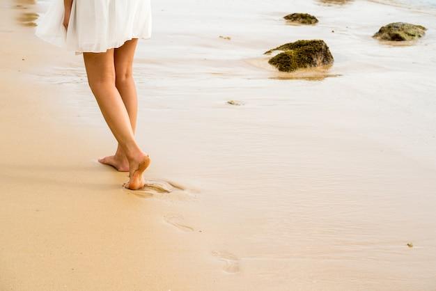 Женщина ходить по пляжу, печать ноги на текстуру песка, скопировать пространстве. Premium Фотографии