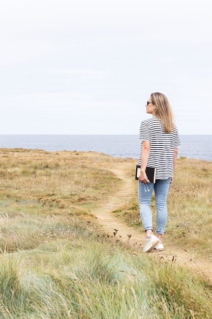 海の前の道を歩いている女性 Premium写真