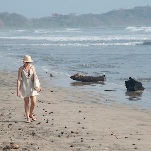 Женщина, идущая вдоль побережья в коста-рике Premium Фотографии