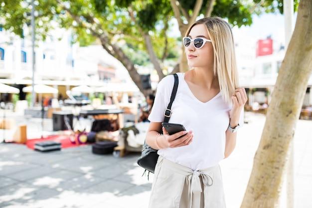晴れた夏の日に通りを歩いてスマートフォンを使用している女性 無料写真