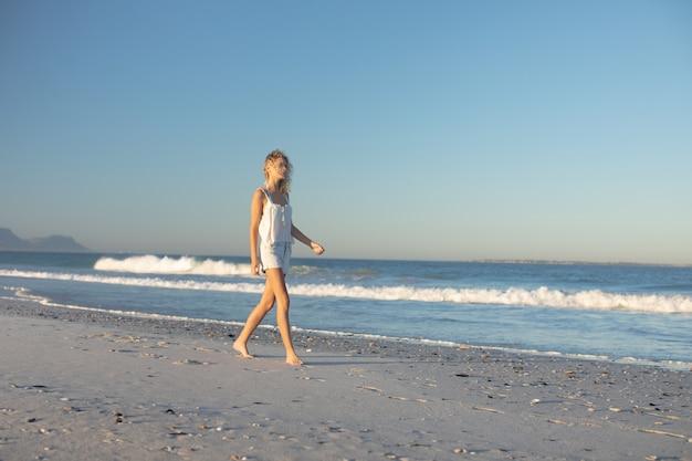 Женщина гуляет босиком по пляжу Бесплатные Фотографии