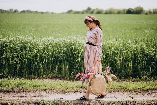 Woman walking in a field with lupinuses Free Photo
