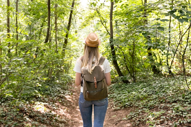 Woman walking in forest from behind Free Photo