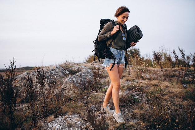 Woman walking in the mountains with travel bag Free Photo