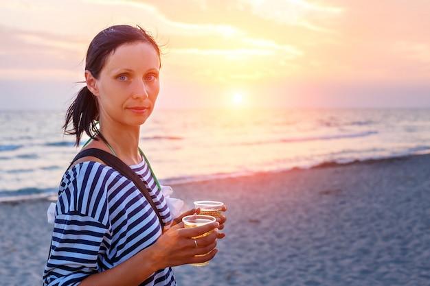 夕暮れ時のサーフィンのビーチの上を歩く女性 Premium写真