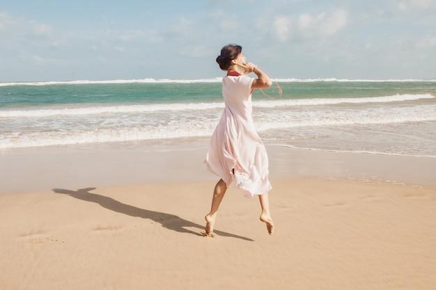 ビーチの砂の上を歩く女性 無料写真