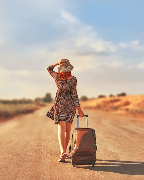 Woman walking on the road with luggage. freedom concept Premium Photo