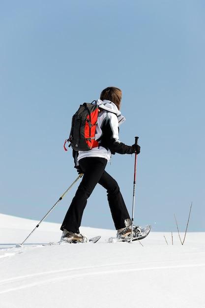 Donna che cammina nella neve con le racchette Foto Gratuite