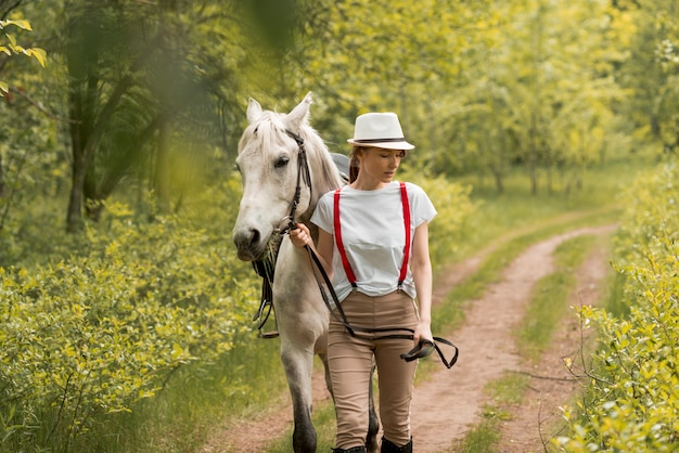 Woman walking with a horse in the countryside Free Photo