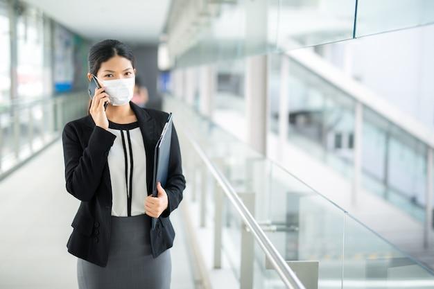 サージカルマスク顔の保護歩行と歩いている女性と空港鉄道駅の仕事で群衆の中に目をそらすビジネスを求めて通勤します。 Premium写真