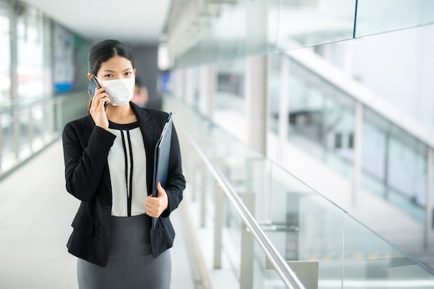 Woman walking with surgical mask face protection walking and calling for business looking away in crowds at airport train station work commute to hospital. Premium Photo