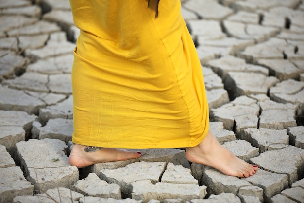 A woman walks barefoot on the dry ground. Premium Photo