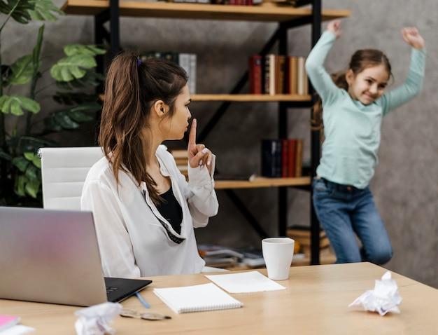 Женщина хочет спокойно работать, так как ее дочь шумит Бесплатные Фотографии