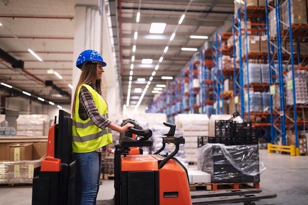 대형 유통 창고 센터에서 지게차 기계를 운영하는 여성 창고 작업자 무료 사진