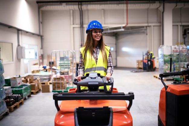 대형 물류 창고 센터에서 지게차 기계를 운전하는 안전모 및 반사 안전 장비가있는 여성 창고 노동자 무료 사진