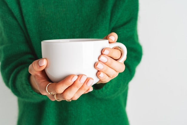 Woman in warm wool green sweater is holding white mug in her hands with tea. mock up for winter mood design. minimal style. Premium Photo