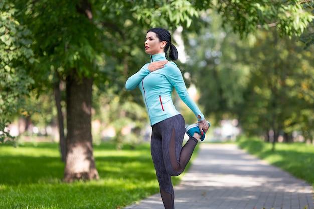 Женщина разогревает мышцы перед бегом на открытом воздухе в летнее время Premium Фотографии
