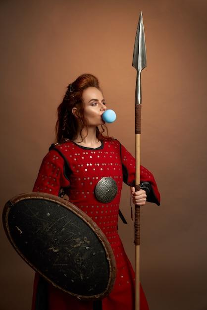 Женщина-воин дует большой синий жевательная резинка. Бесплатные Фотографии