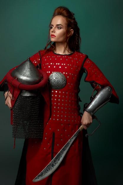 Женщина-воин позирует с кинжалом, шлем в руке. Бесплатные Фотографии