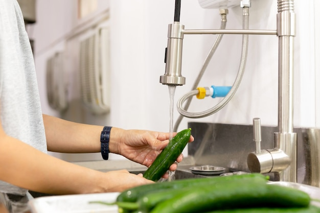 Premium Photo Woman Washing Cucumbers In Running Water In Kitchen Sink