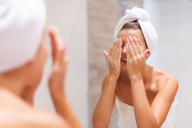 Woman washing face in bathroom Free Photo