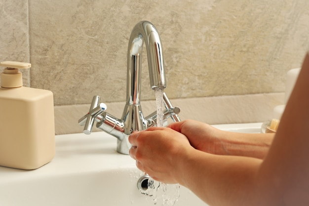 Woman washing hands under the water tap in sink Premium Photo