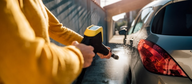Woman washing her car with pressure washer Premium Photo