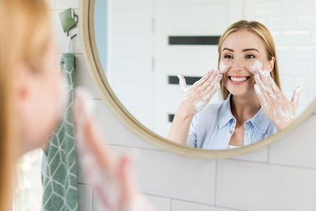 Женщина моет лицо в зеркале в ванной Premium Фотографии