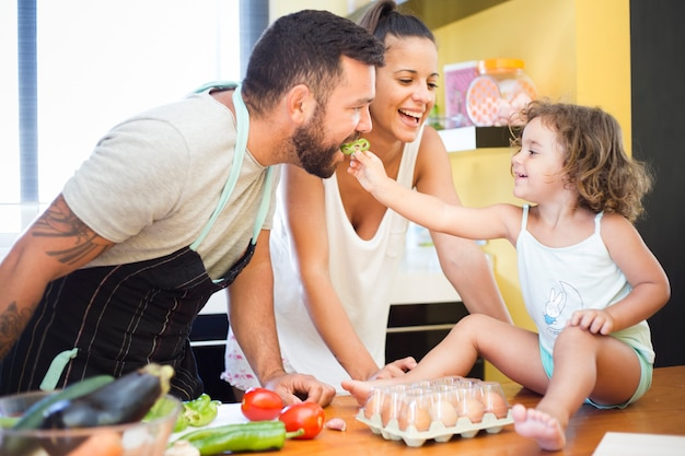 Woman watching daughter feeding bell pepper to her father Free Photo