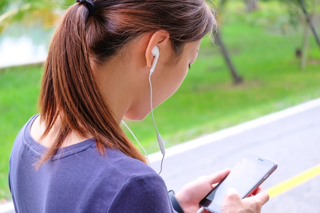 A woman watching her a smart phone for selection the music before exercise. Premium Photo