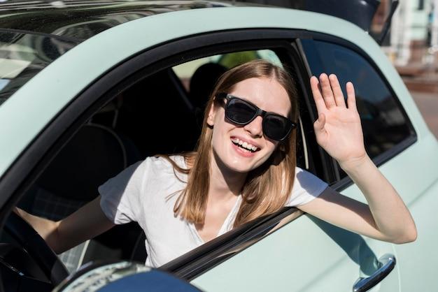 航海前に車から手を振っている女性 無料写真