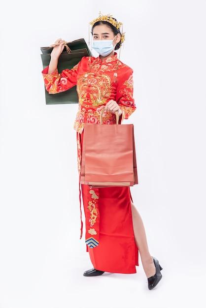 女性は中国の旧正月の買い物からチャイナドレスとマスクホールド紙袋を着用します 無料写真