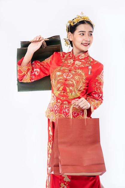 中国の旧正月の買い物から紙袋とチャイナドレスの笑顔を着ている女性 無料写真