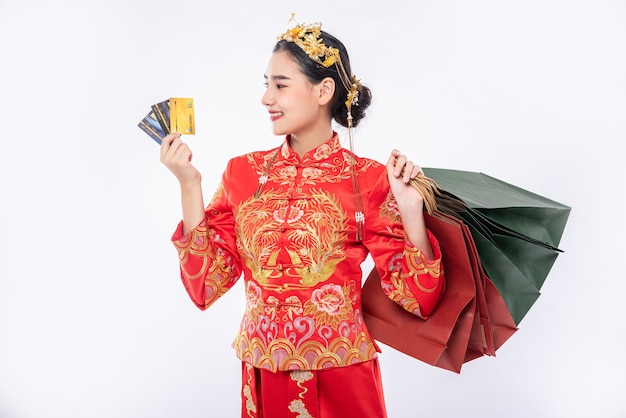チャイナドレスを着た女性がクレジットカードを使って旧正月の買い物をする 無料写真