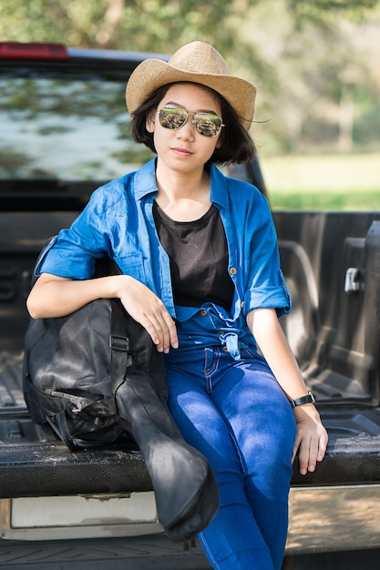 Woman wear hat and carry her guitar bag on pickup truck Premium Photo