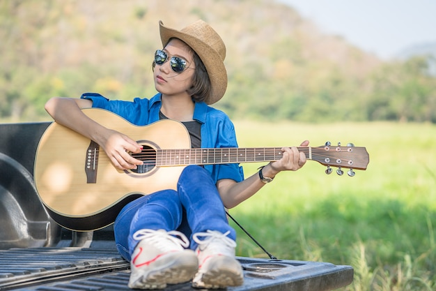 Woman wear hat and playing guitar on pickup truck Premium Photo