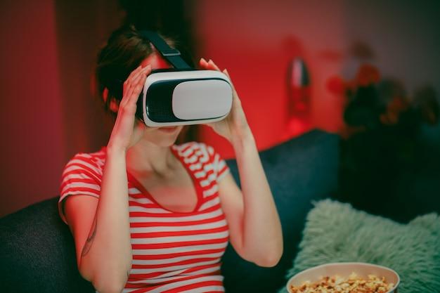 Женщина носить гарнитуру vr, играя в видеоигры. женщина расслабляющий играть в видеоигры, используя гарнитуру vr. кавказская женщина геймер. Premium Фотографии